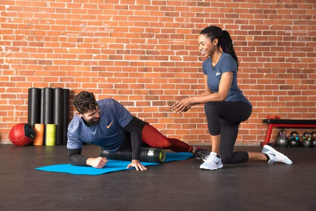 Personal Trainer Working with Client Who is Foam Rolling