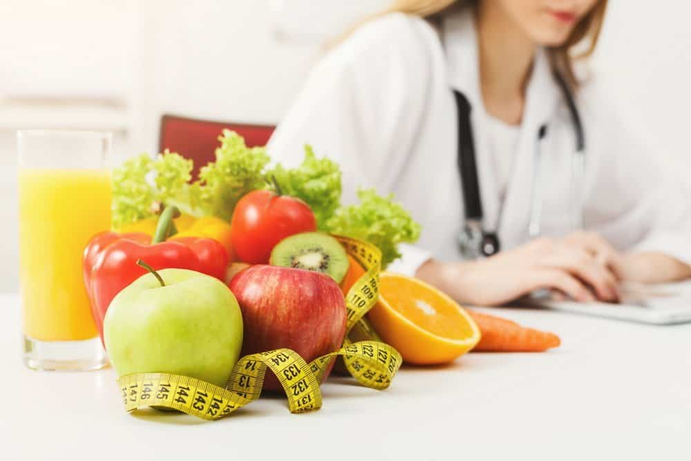 Nutritionist desk with healthy fruit, juice and measuring tape. Dietitian working on diet plan. Weight loss and right nutrition concept